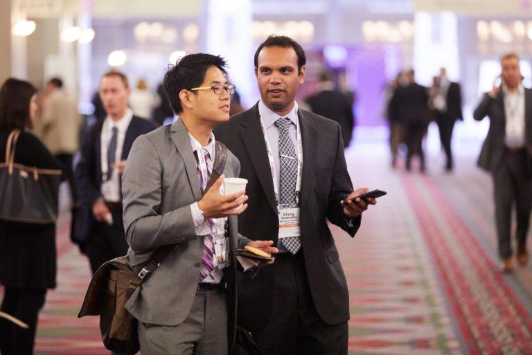 business men in suits talking with smart phones